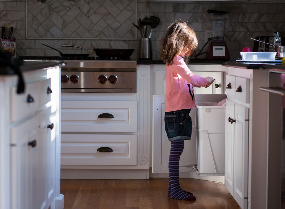 Side view of girl sharpening pencil over garbage bin in kitchen