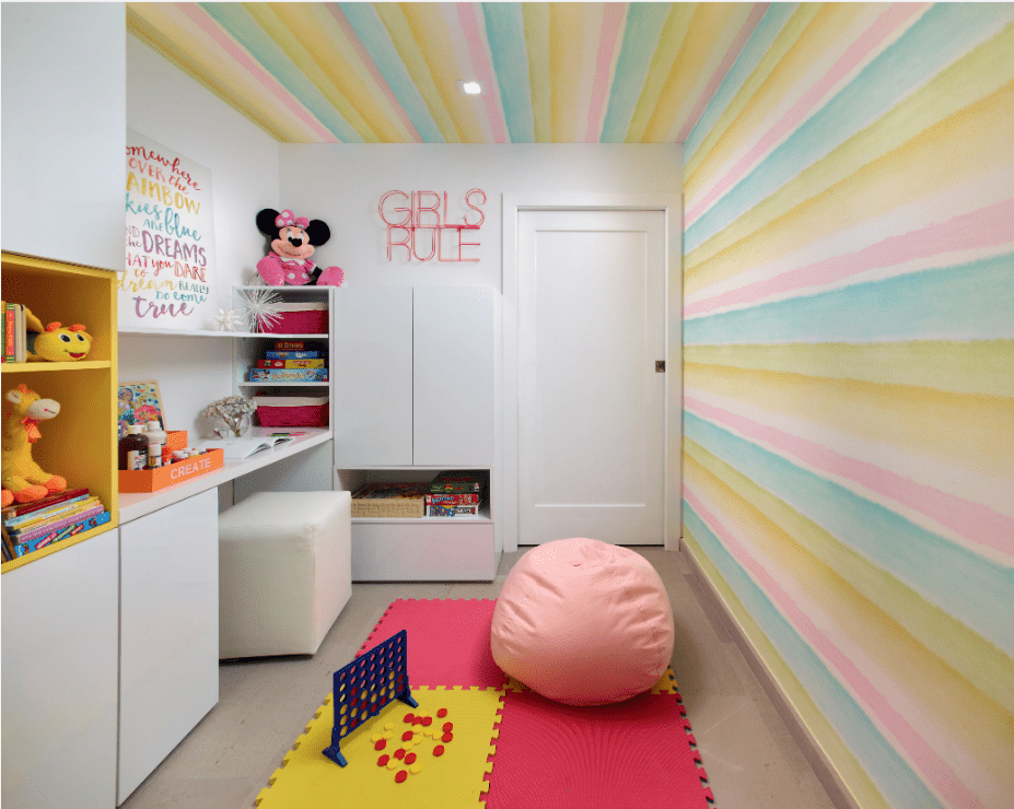 A pastel-striped wallpaper mural extends to the ceiling in this young girl's bedroom