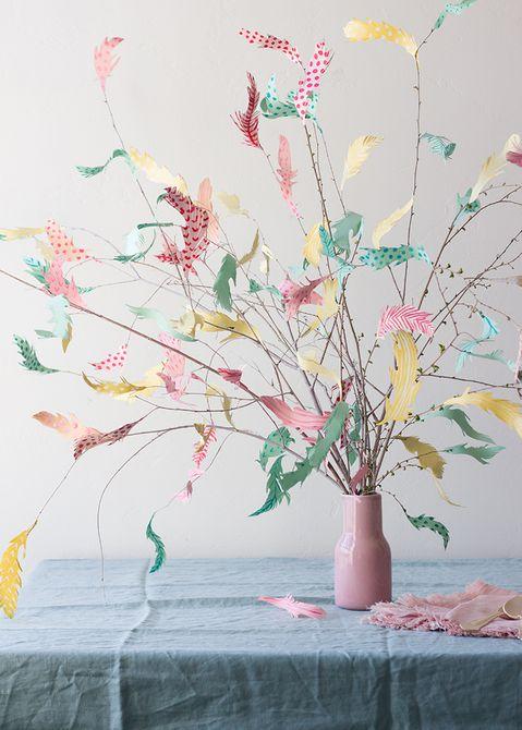 Ramas con plumas de papel en un florero