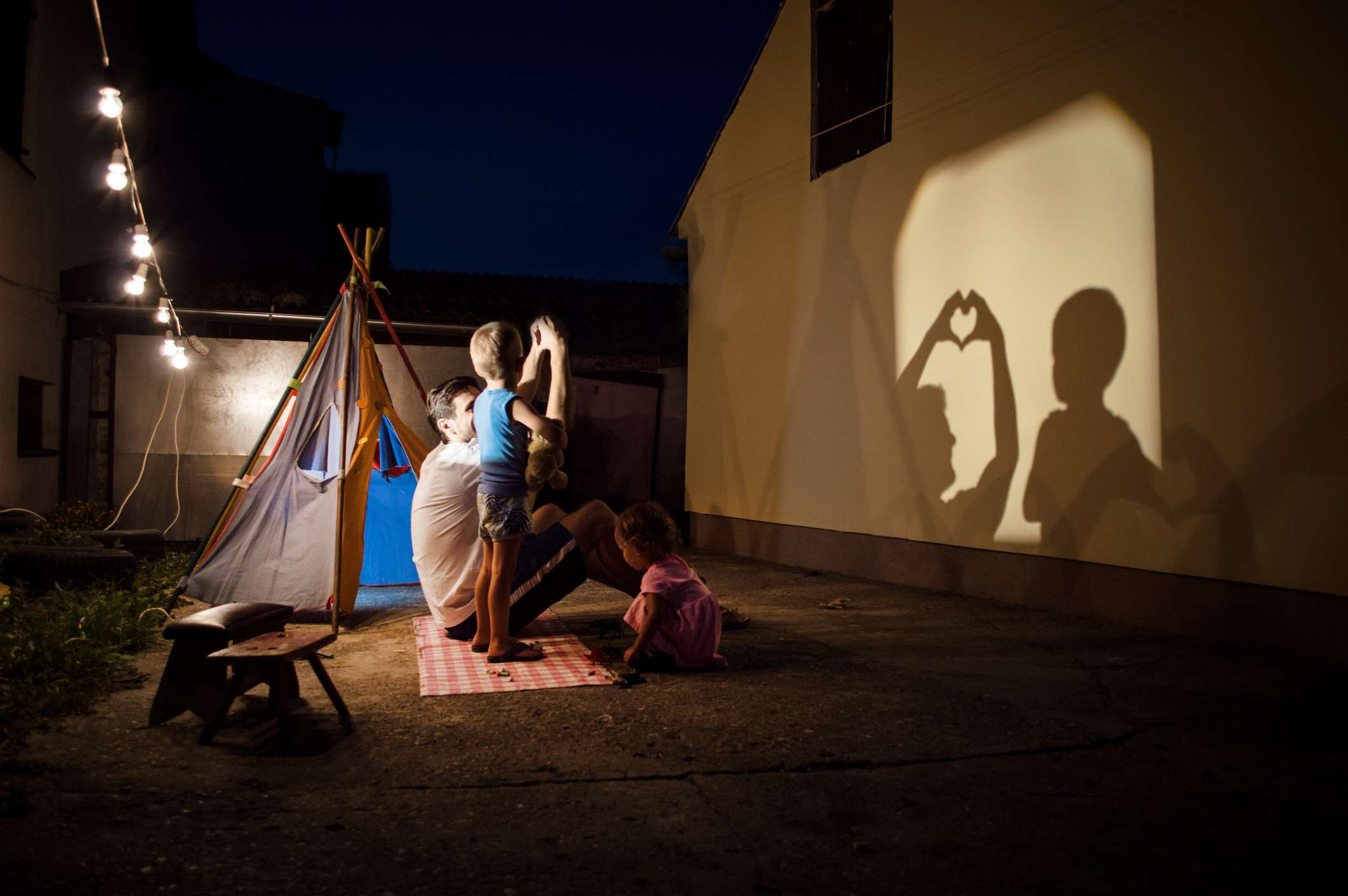 Family with young children playing with shadow puppets