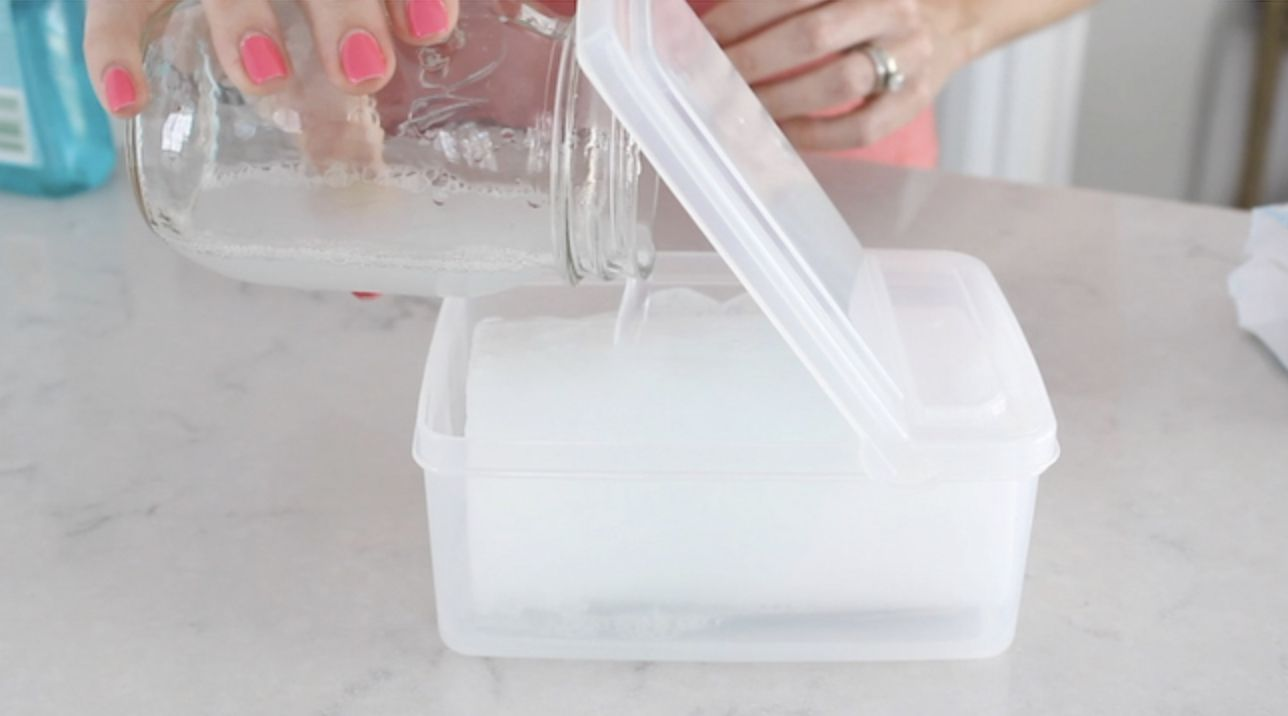A woman pouring liquid into a clear tub