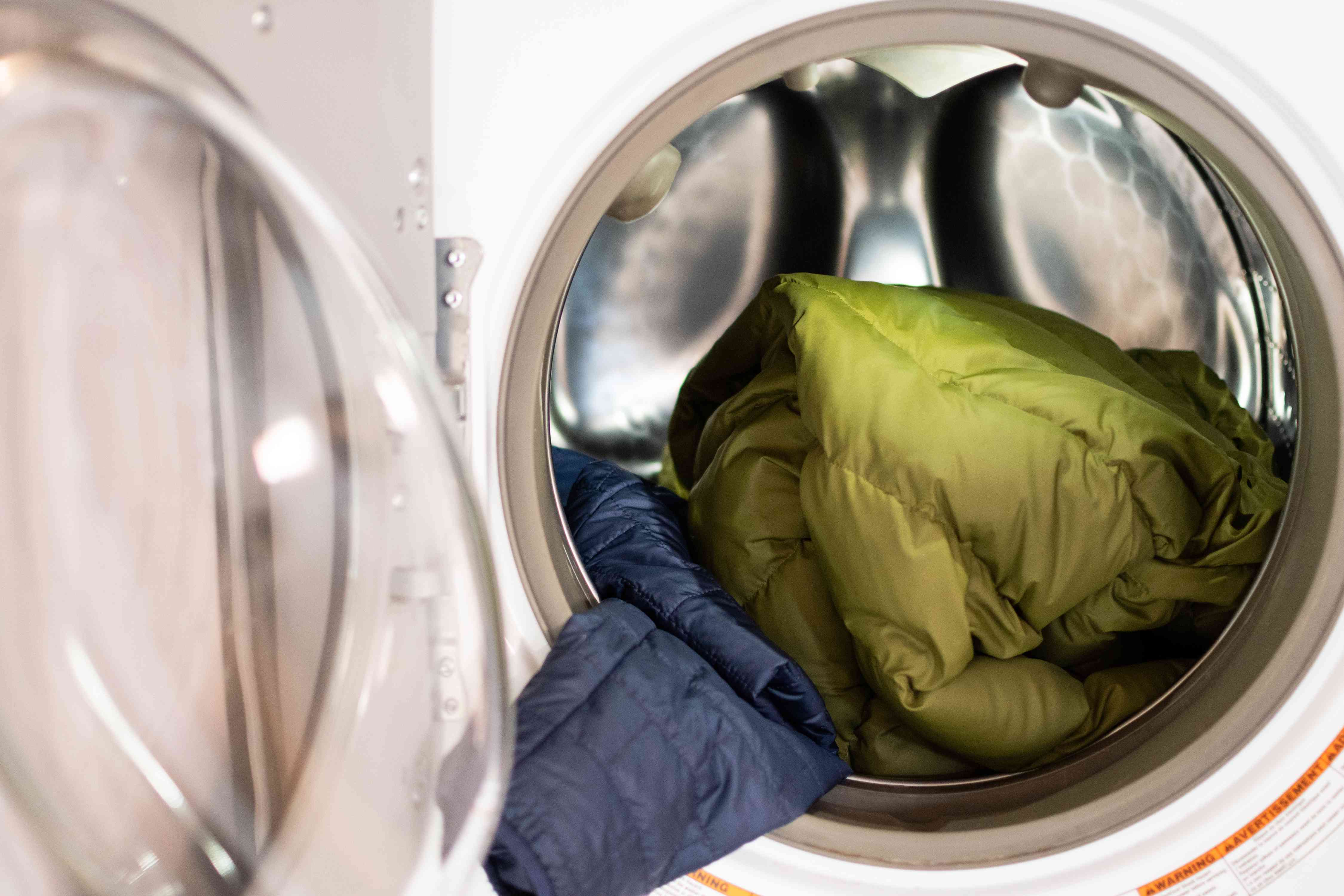 Green and blue down coats inside front facing washing machine