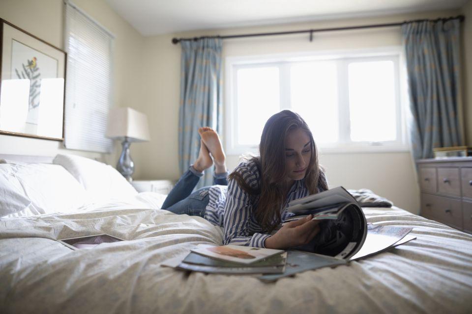 Teenage girl reading magazines on bed