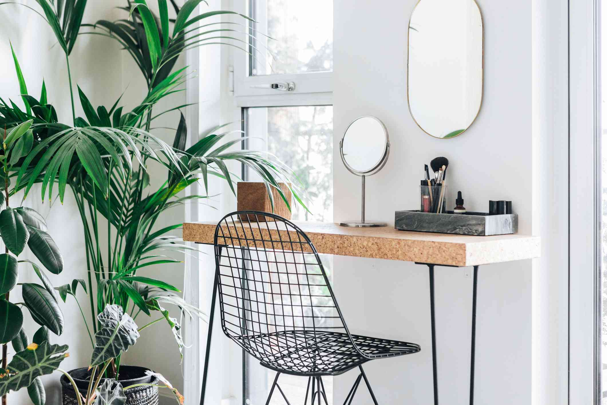 A corner of the modern, stylish and bright bedroom with plants and mirror