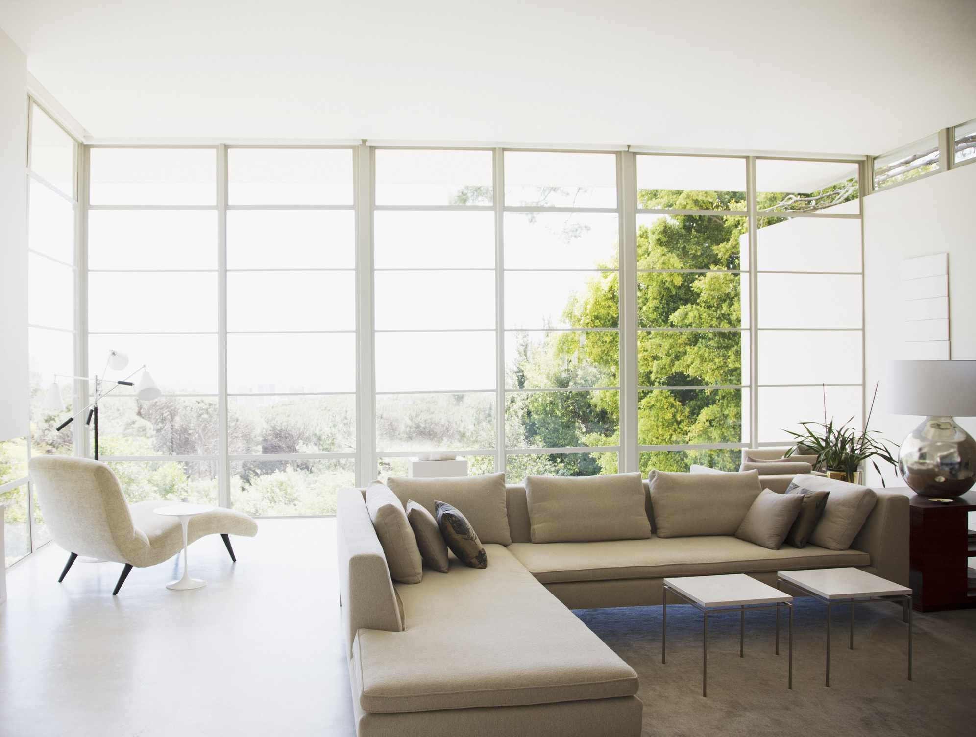 Living room with large windows facing greenery