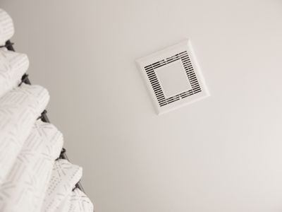 Bathroom exhaust fan in ceiling above shower curtain