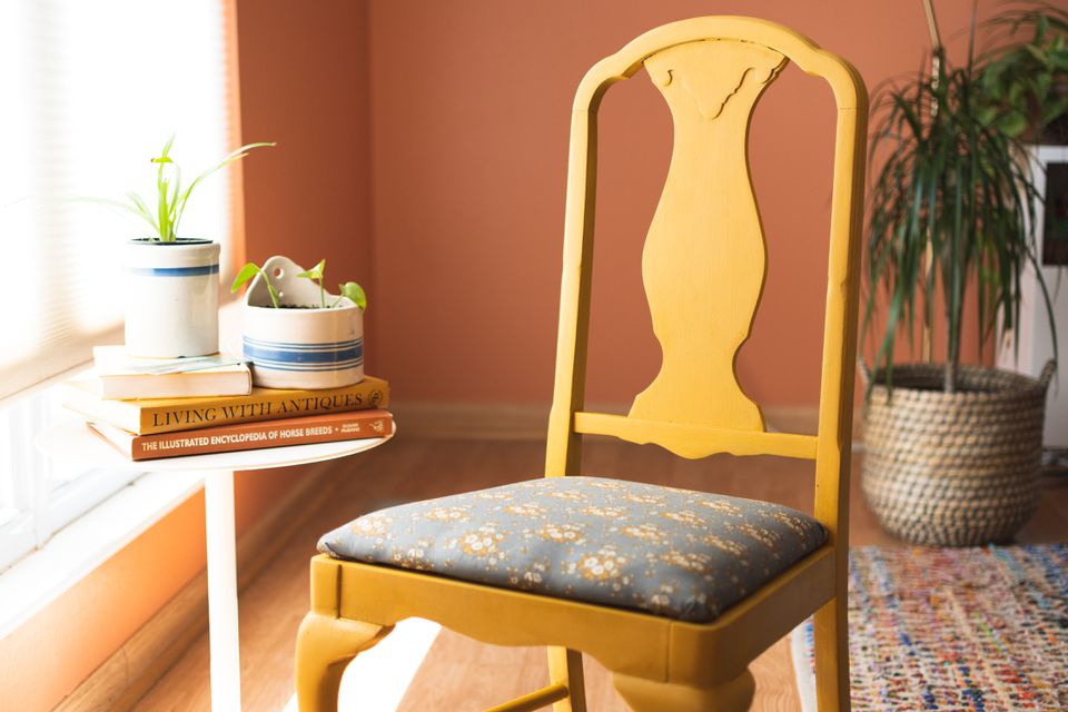 Refurbished wooden chair next to white table white books and houseplants by light-filled window