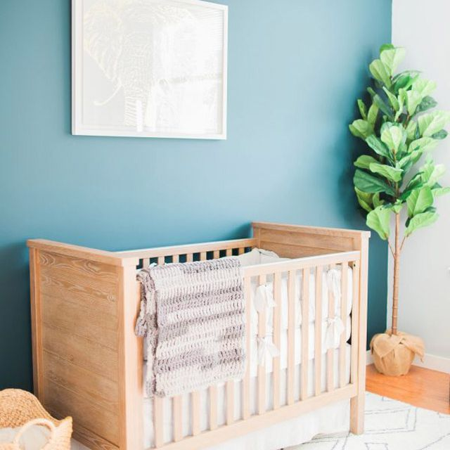 Simple, gender-neutral nursery with teal accent wall