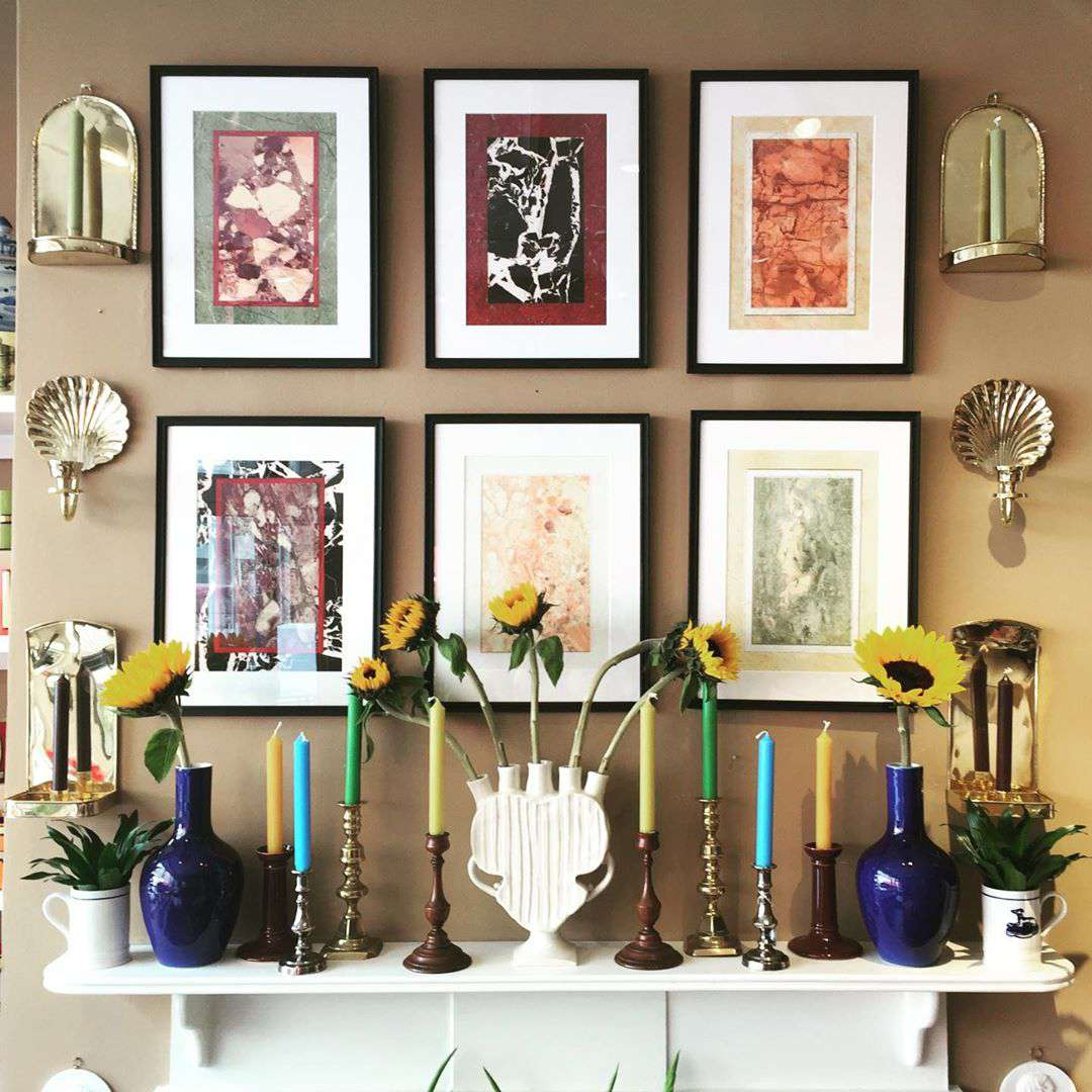 Light brown wall with framed pictures on it