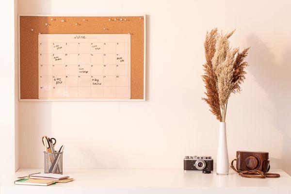 Organized desk with wall calendar