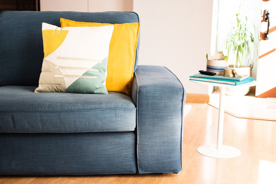 Couch with dark blue upholstery and yellow and white pillows on right side