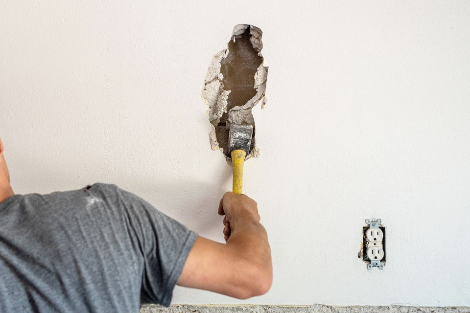White wall being demolished with yellow hammer for home renovation