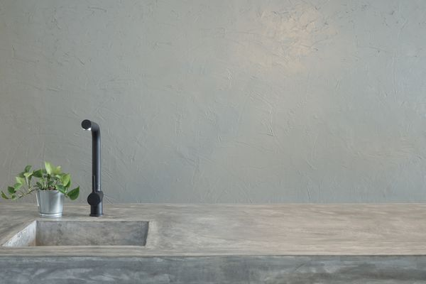 Concrete countertops against white wall in an empty kitchen.