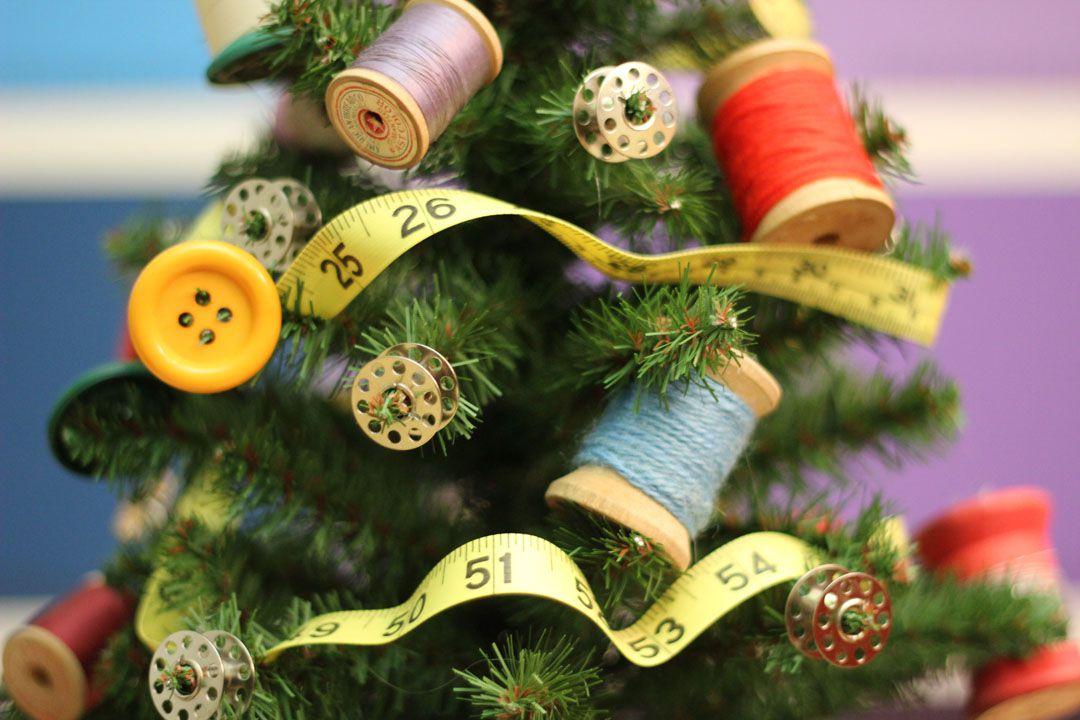árbol de Navidad adornado con suministros de costura, incluyendo bobinas, botones, hilo y cinta métrica