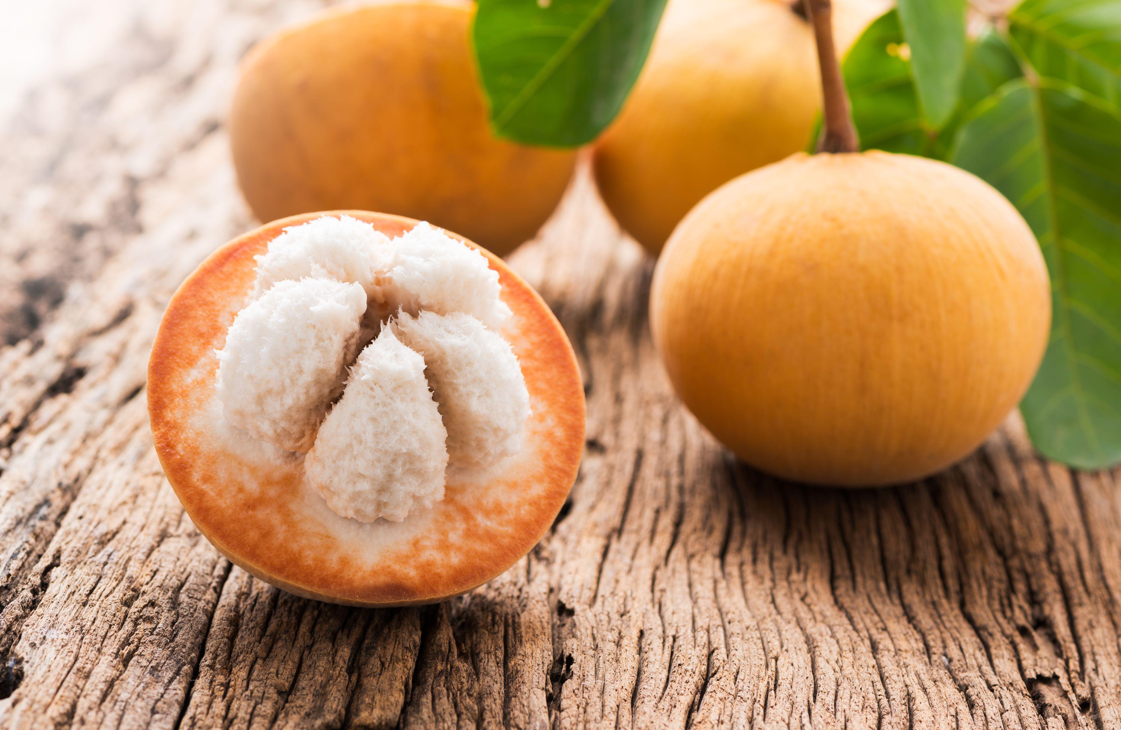 sliced santol fruit on wooden background