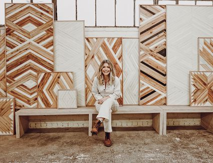 Aleksandra Zee poses with some of her wood art panels