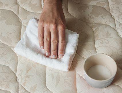 person blotting a mattress