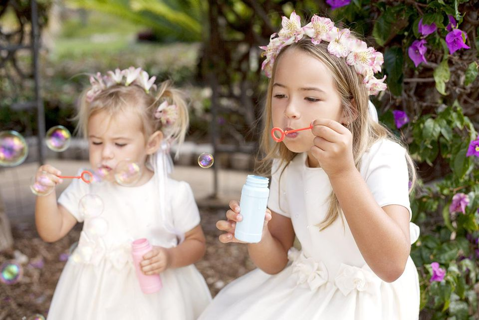 Sister flower girls blowing bubbles