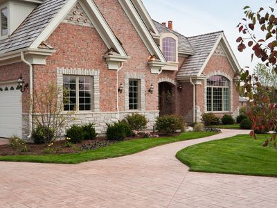 A brick driveway and walkway to a brick house