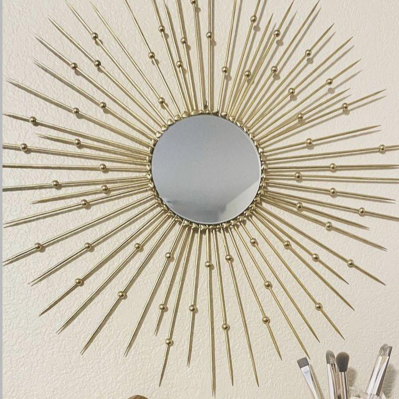 a DIY sunburst mirror frame using sticks and beads