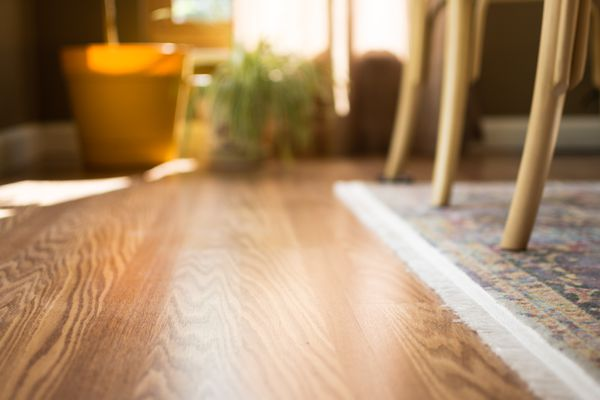 Laminate wood floor with rug and chair legs closeup