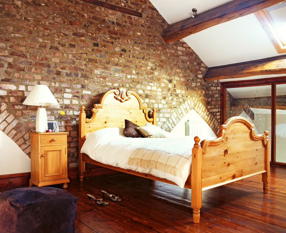 A double bed with a wooden frame is placed in a loft