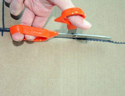 Persona que usa tijeras para cortar el cartón