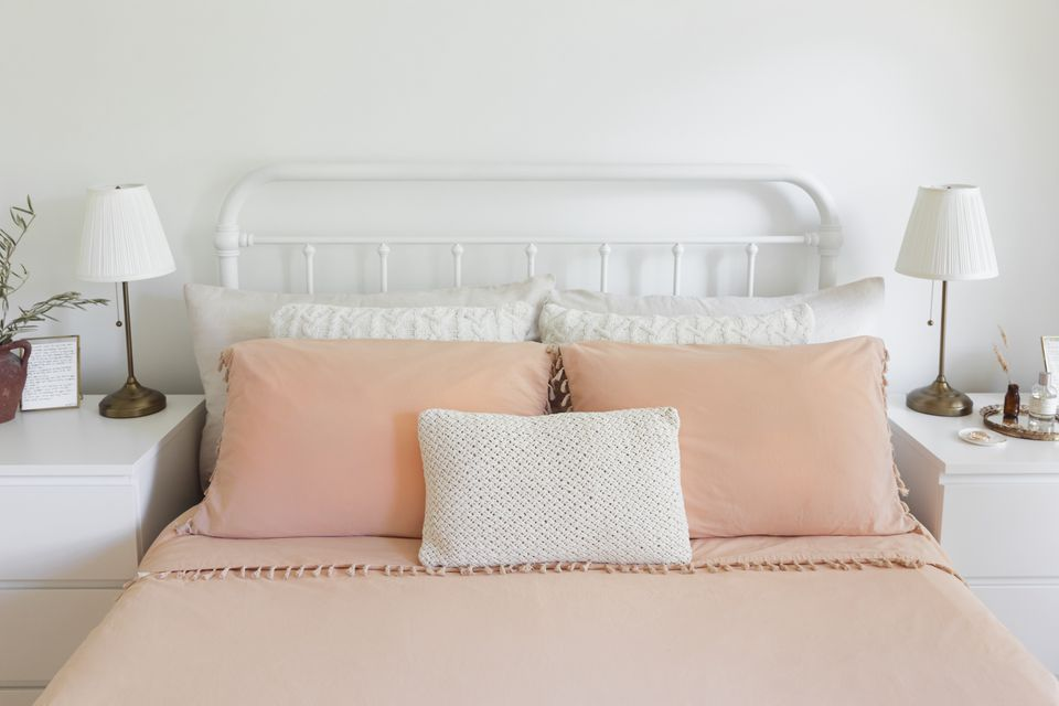 Made bed with peach and white colored sheets and pillows next to white nightstands and metal headboard