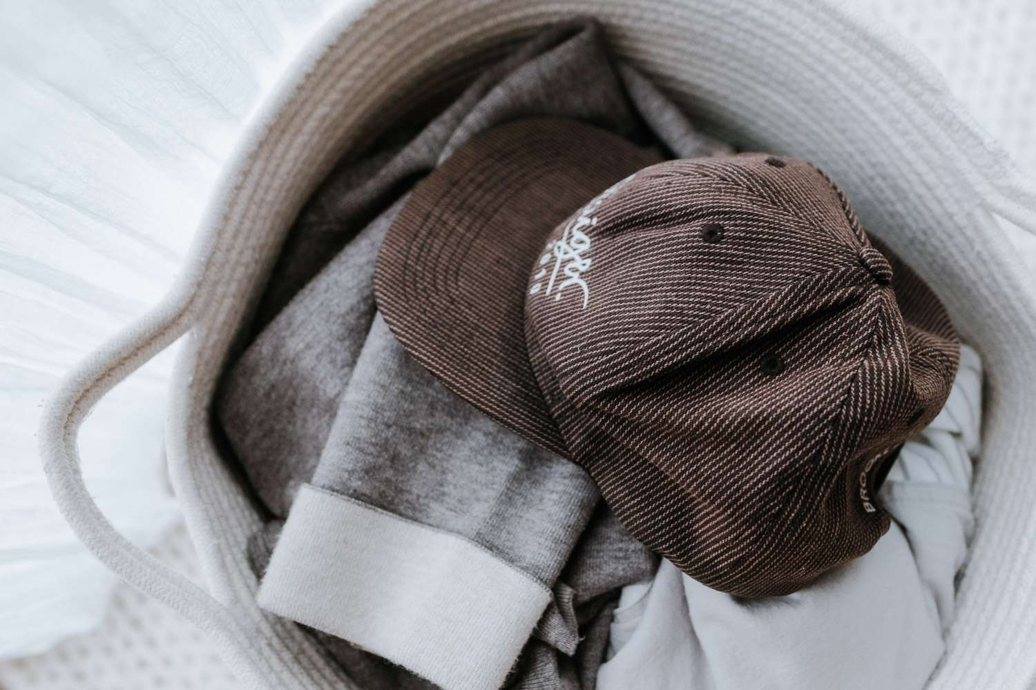 A baseball cap sitting on a pile of laundry in a basket