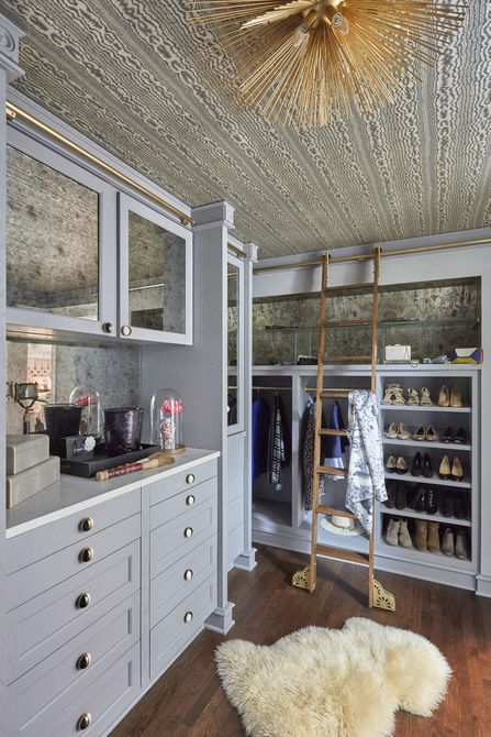 gray walk-in closet with gold light fixture