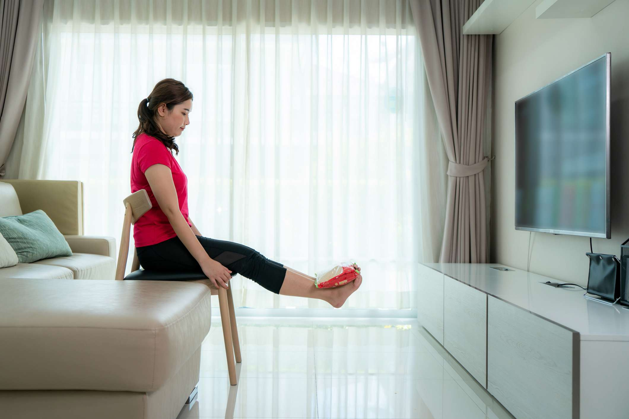Asian woman finding new ways to use everyday objects around the home as substitutes for her regular exercise equipment she using Leg lifts with ankle weights fashioned out of bags of rice at home.