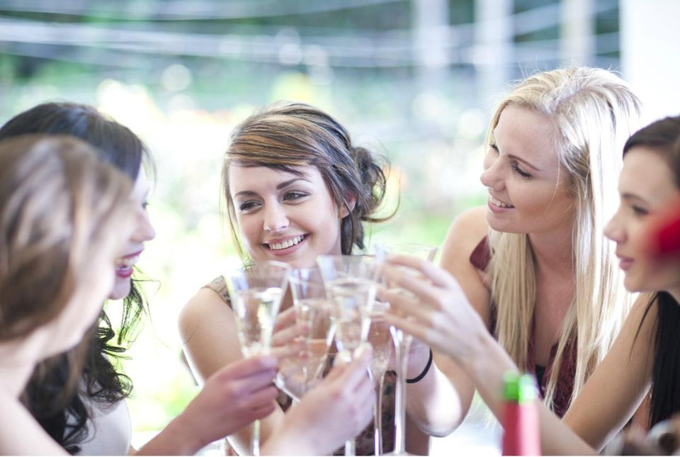 Young woman and friends toasting with glass of champagne