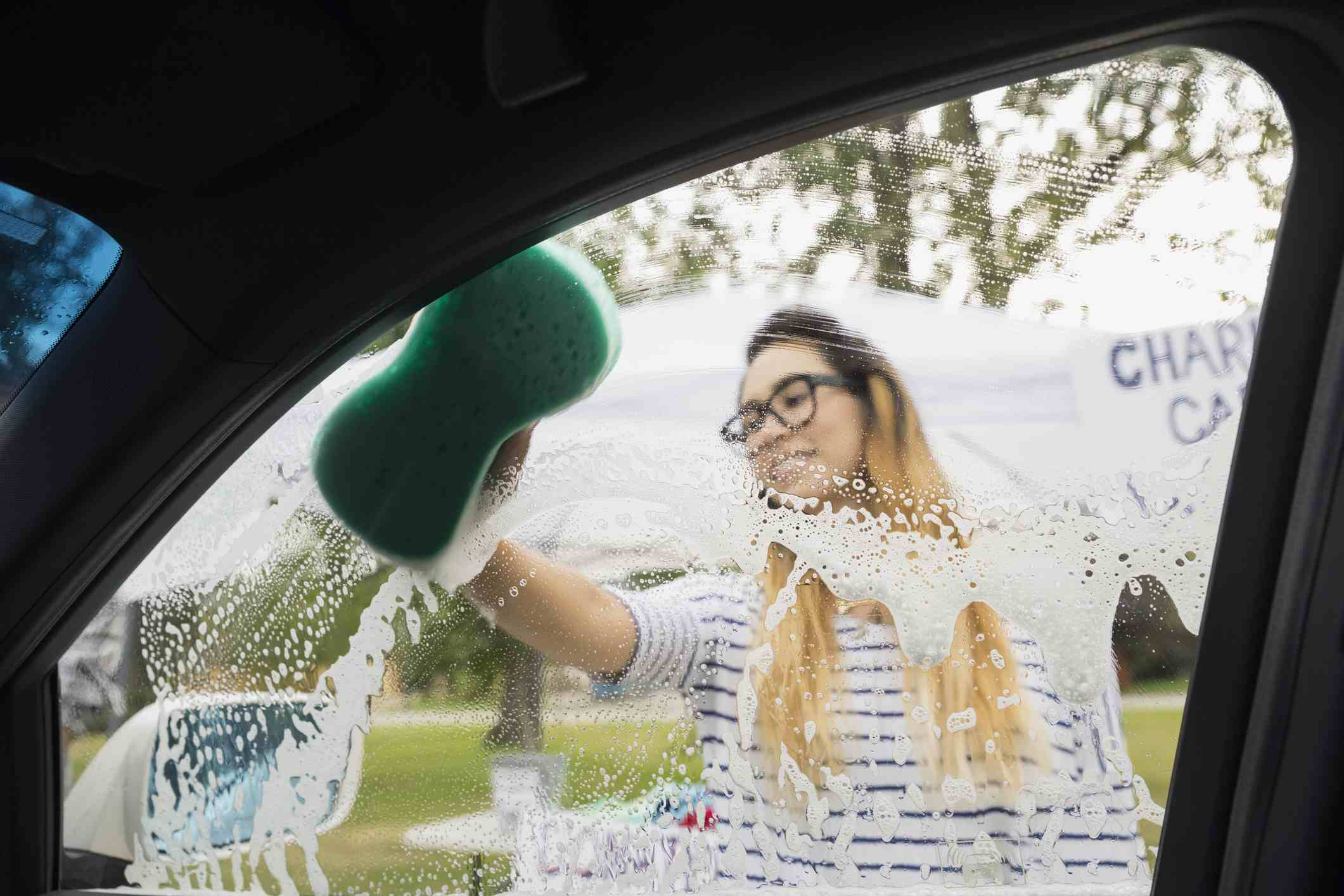 person using a sponge on a car window