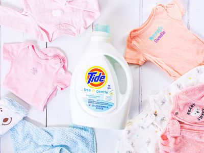 Baby clothes laid on white wooden surface around a white Tide laundry detergent bottle