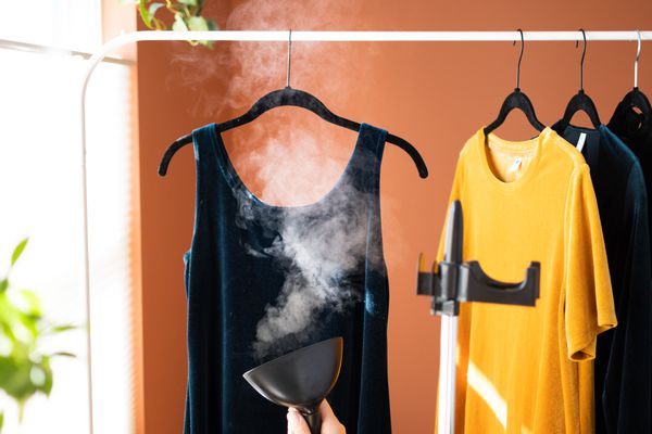 Navy blue velvet dress hanging on clothes hanger while being steamed by hand