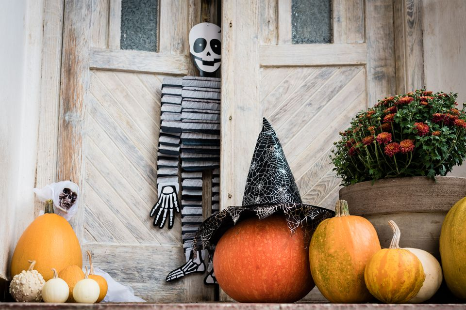 front door decorated for Halloween with various pumpkins and skeletons