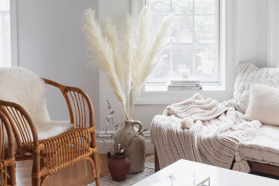 Cream-colored pampas grass in beige vase in between wicker chair and seating with blanket on top