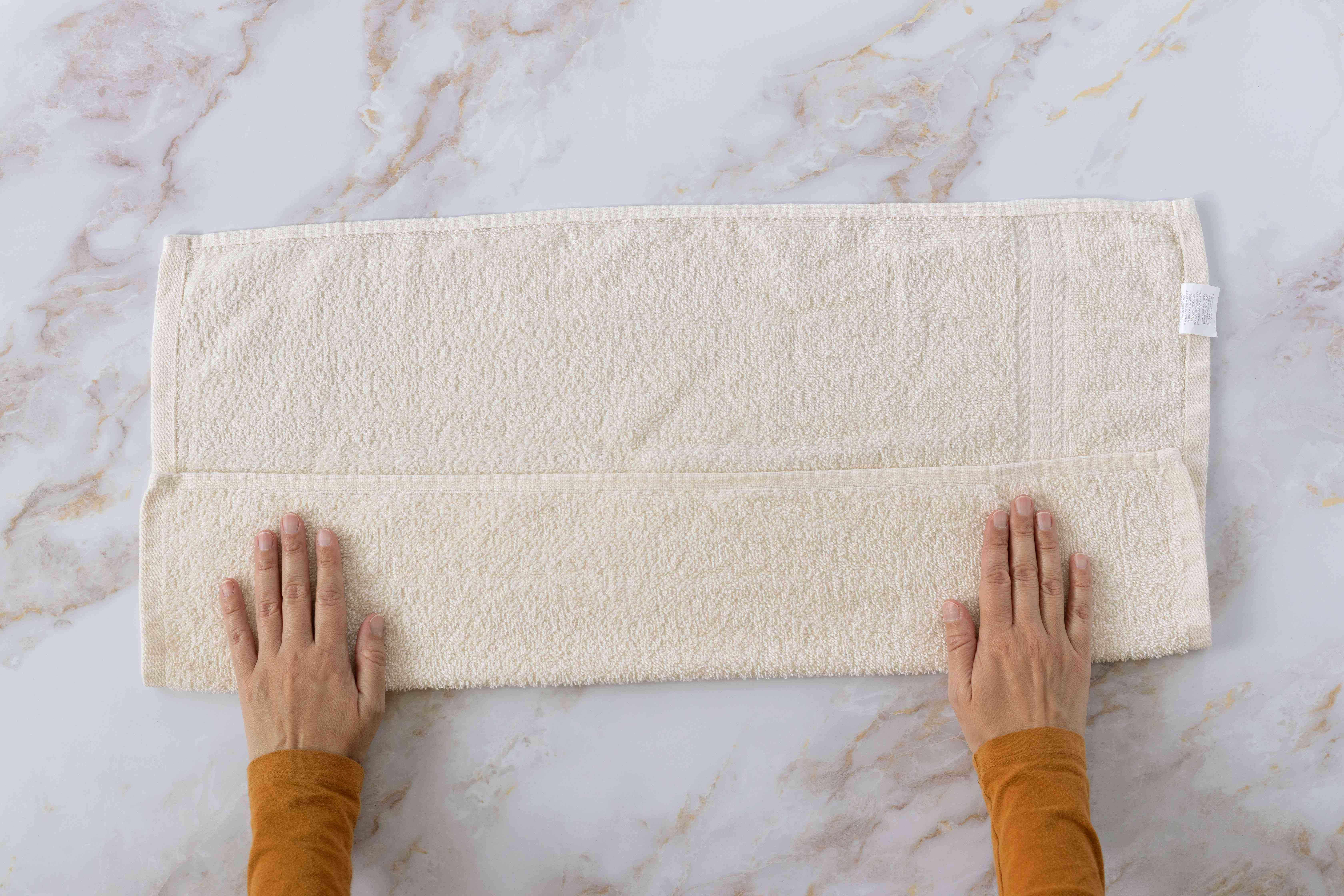 Cream towel laid flat with one third folded