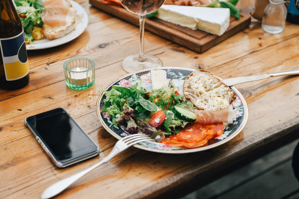 Close-up of healthy food served in plate by mobile phone on table during party