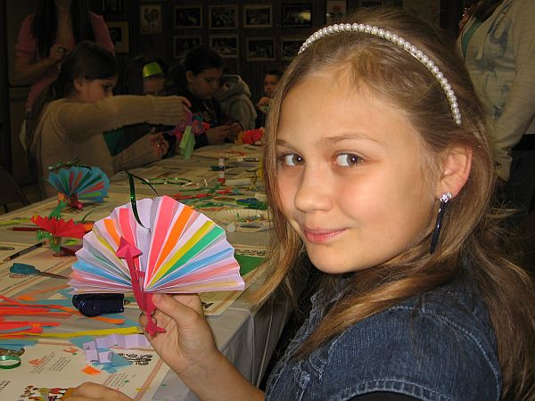 A Young Girl Holding a Paper Peacock Christmas Ornament
