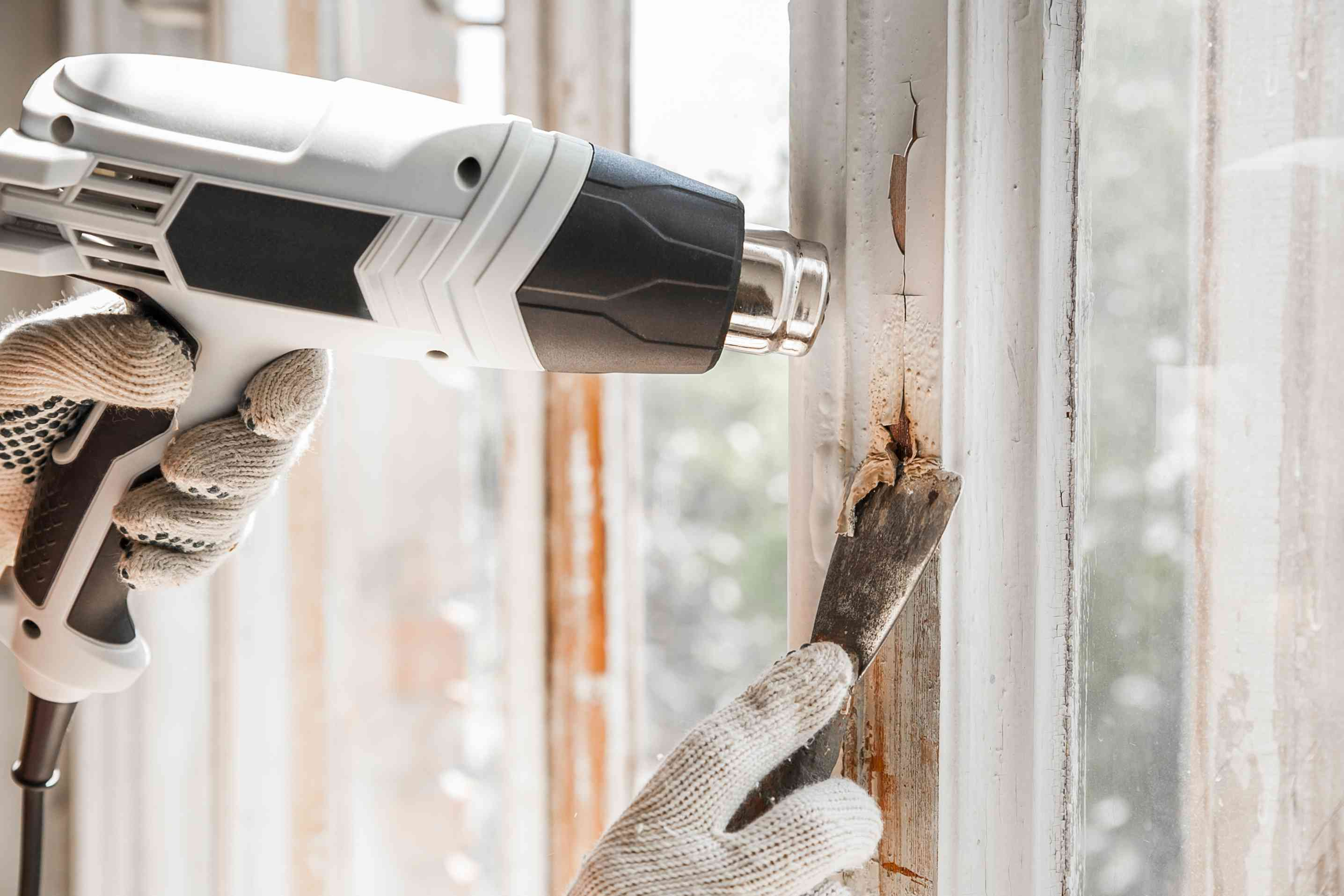 person removing old paint from a window with a heat gun and scraper
