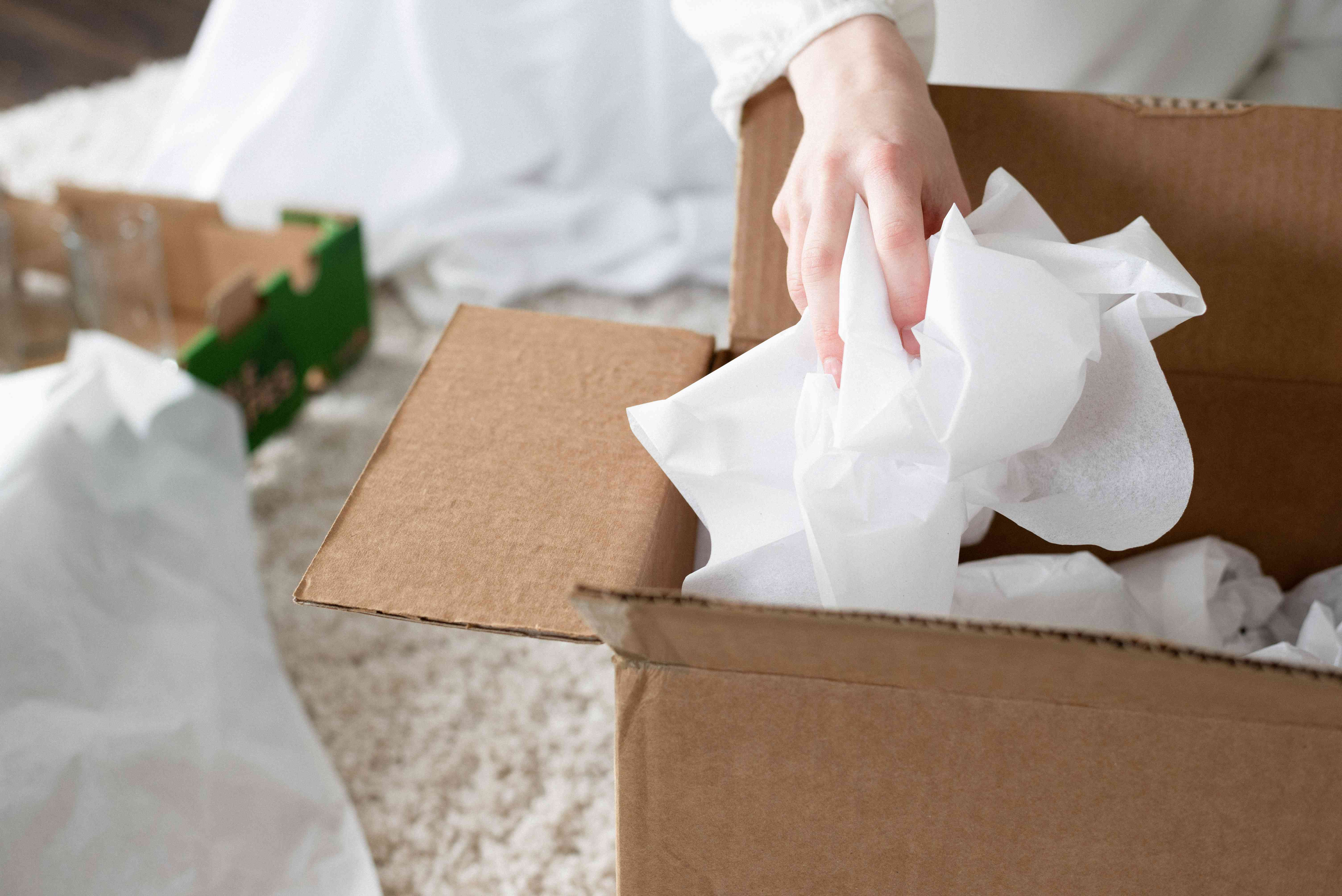 person adding extra packing paper to the top of the box