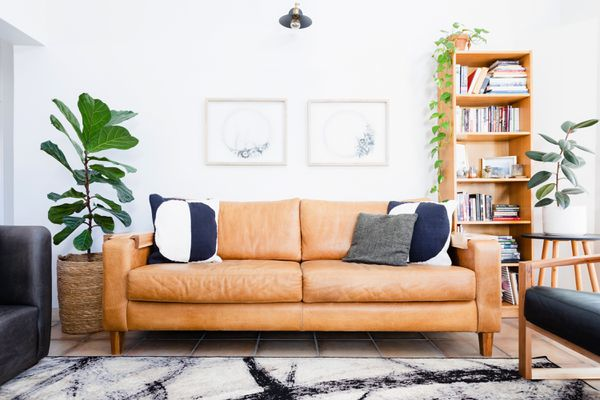 Brown leather couch with blue and white pillows in decorated living room with houseplants