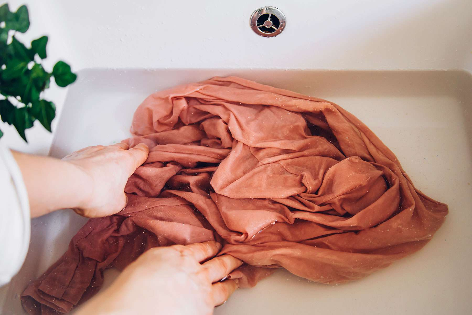 person soaking the garment in a sink