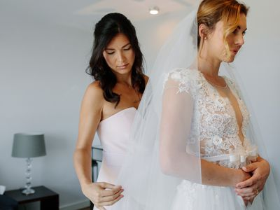 Bridesmaid helping bride to put on a veil