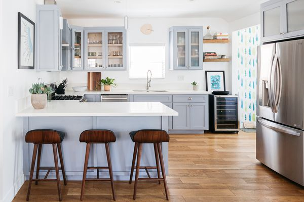 Small kitchen with white countertops and gray-blue cabinets near stainless steel refrigerator