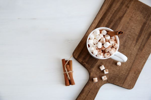 Top view mugs with hot chocolate and marshmallows on chopping board near cinnamon.