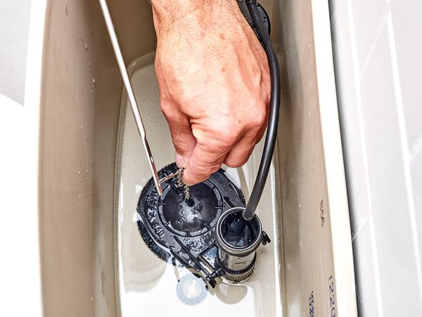 Toilet flapper being replaced inside toilet tank with water