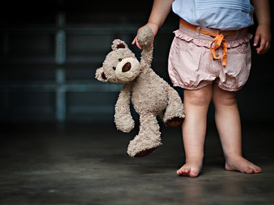 Low section of a girl holding her teddy bear