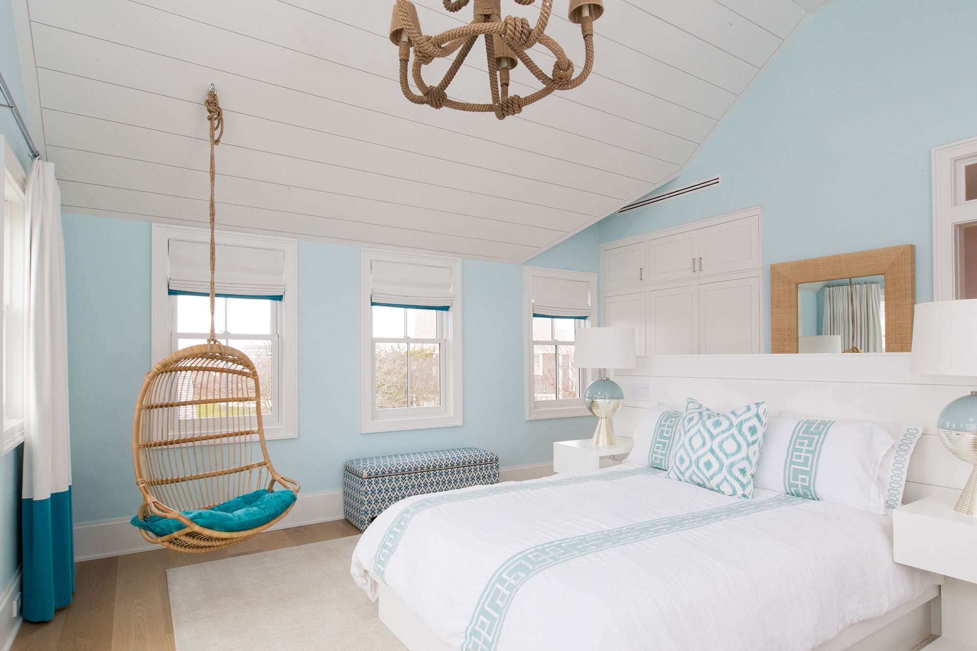 Beach inspired bedroom with rattan swing chair